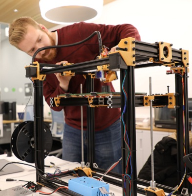 Stian French makes adjustments to the 3D printer he created in the Maker Studio