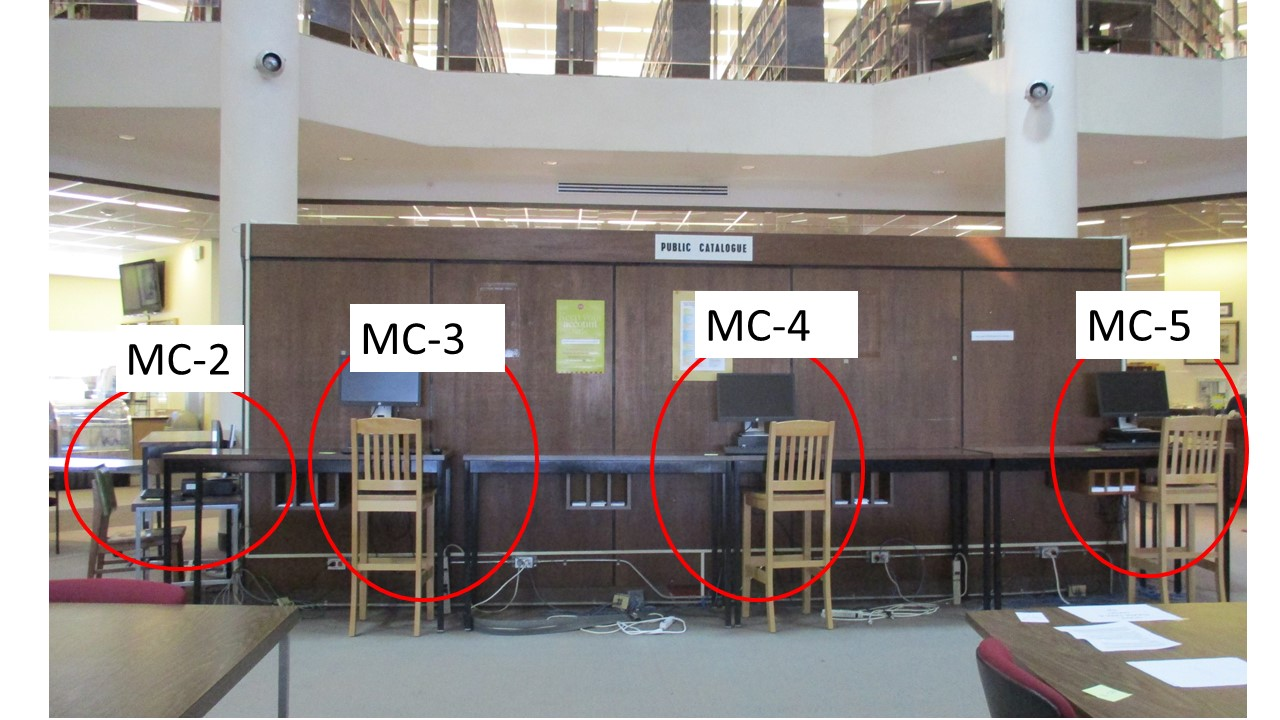 Photo of computers with bar stools and numbered seats