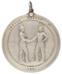 """front of medal for Treaties 1 & 2, third version of medal dated 1873, """"a stylized Indian encampment at sunset, with an Indian leader in war costume and a British officer shaking hands"""""""