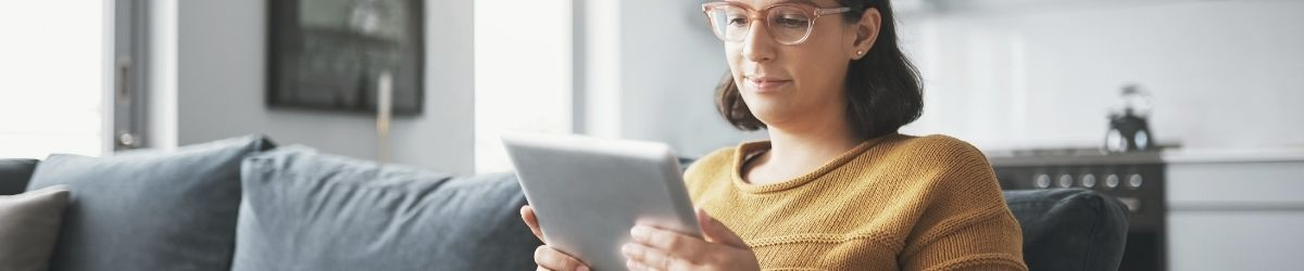 Woman holding a tablet and looking at screen