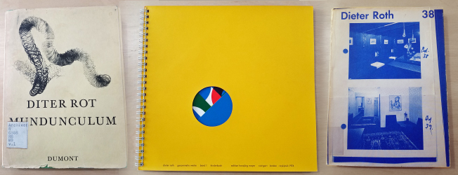 Three books by Dieter Roth: a white cover with elongated abstract sketch, a yellow cover with a circle cut out to show colored pages, and a white book with blue photos of galleries.