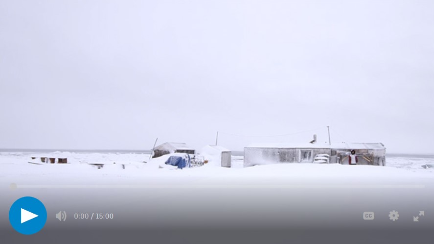 Snow-covered landscape with building, sheds, and one person