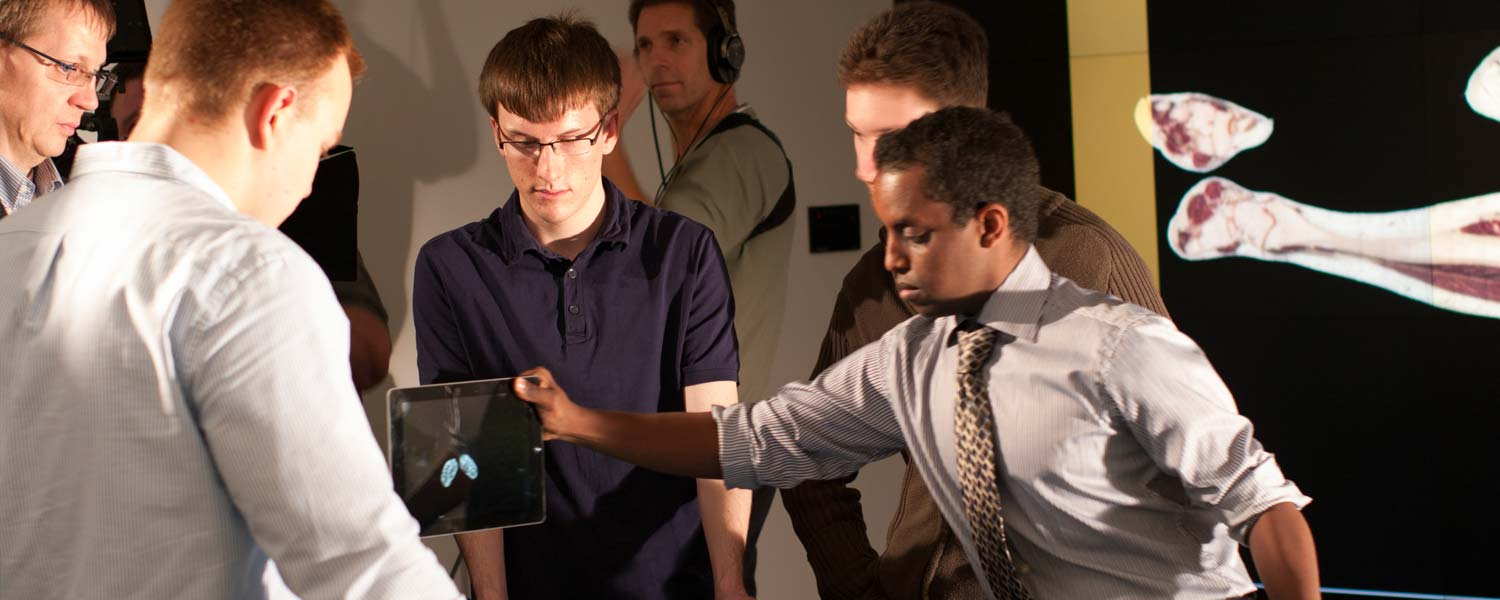 Class of computer science students using touch table in visualization studio