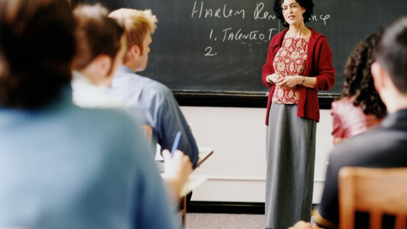 instructor standing at the front of a class full of students