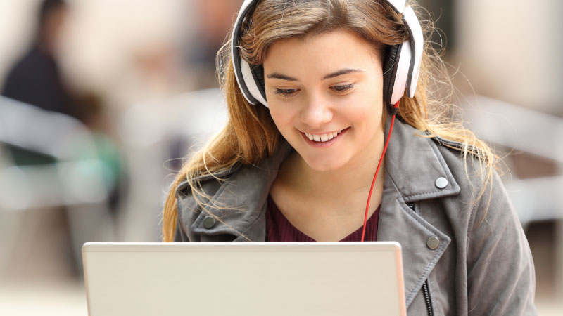 Student wearing headphones smiling and looking at laptop